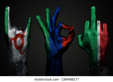 a set of three hands with a painted flag of Ingushetia, Dagestan and Chechnya show middle finger, goat and Okay, a sign of aggression, protest and approval on a dark background. Horizontal frame