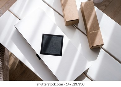 Set of three long package boxes in brown craft paper and white and black. Brand packaging mockup. Overhead. Beauty, fashion blogging, minimalism concept
