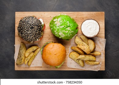 set of three mini homemade Burger with marble beef and vegetables on a wooden Board. the concept of junk food and fast food on dark concrete background. Top View