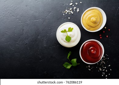 Set of three sauces - mayonnaise, mustard and ketchup in white ceramic bowls on  black stone or concrete background. Selective focus. Top view.