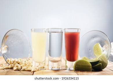 Set of three shot glasses known in Mexico as Bandera and served with lemon juice, tequila and sangria.