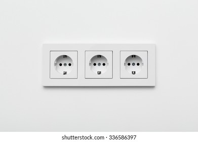 Set of three sockets on the white wall