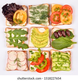 Set with toast bread and different toppings on white background, top view. Toasts with avocado, spinach and other vegetables ingridients. Healthy snack or vegan food concept
