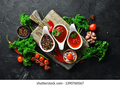 A set of tomato sauces on a black stone background. Ketchup, barbecue sauce, tomato sauce. Top view. Free space for your text.