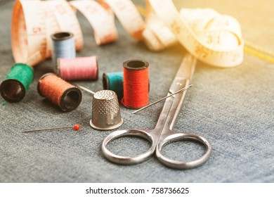 Set of tools and accessories for sewing and needlework with threads in spools, needles, measuring tape and other items on piece of jeans fabric