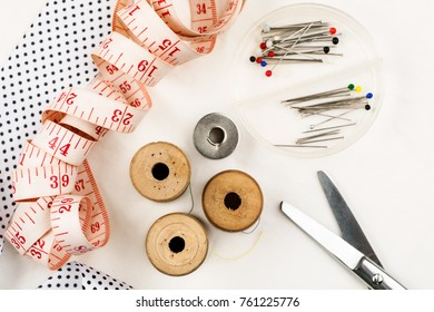 Set of tools and accessories for sewing and needlework with threads in spools, needles, measuring tape and other items on a white background, top view