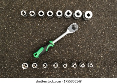 A set of tools, a complete set a six-sided key, a bit, a wrench. cardan joint, screwdriver-holder for bits, screwdriver handle, ratchet, extension cord Gray background