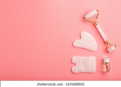 A set of tools for face Massage technique Gua Sha made of natural rose quartz on a pink background. Roller, jade stone and oil in a glass jar for face and body care.