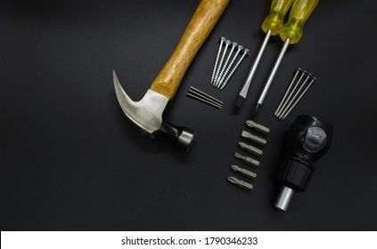 Set of tools, hammer, screwdrivers, nails, screws on a black background.