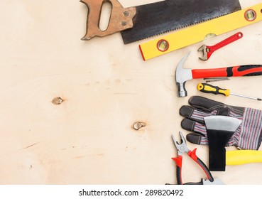 Set of tools for hand repair on a wooden background.