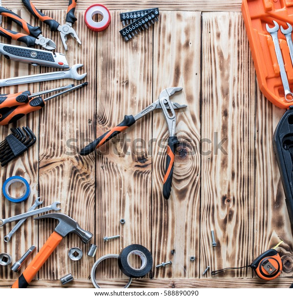 A set of tools on a wooden background. Wrench among different instruments.