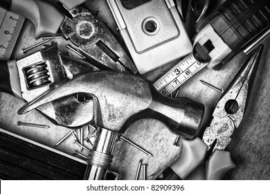 Set of tools over a wood panel on black and white