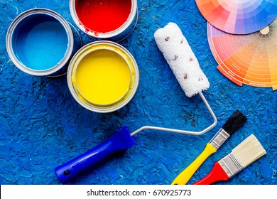 Set of tools for painting on blue wooden desk background top view