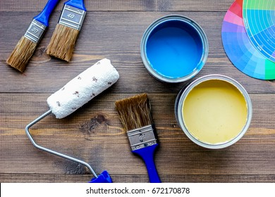 Set of tools for painting on wooden table background top view