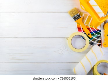 a set of tools for painting and repairing an apartment, brush, adhesive tape and paint rollers. Concept of renovation, choosing and major repair, top view