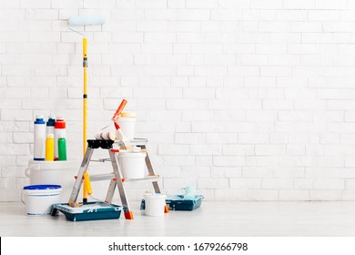 Set of tools and paints for making repair in flat, interior, white bricks wall, copy space