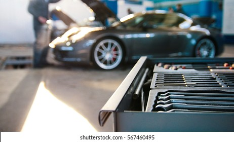A set of tools for repair in car service in front of luxury sport car, wide angle