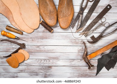 Set of tools for shoemaker on the white wooden background. Copy space.