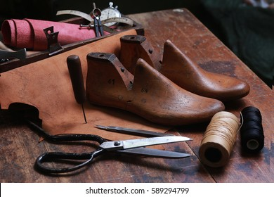 Set of tools for shoemaker on the wooden background.