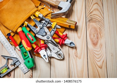 set of tools  in toolbelt on wooden background