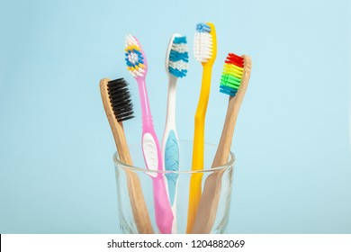 Set of toothbrushes in glass on blue background. Concept toothbrush selection, bamboo eco-friendly and plastic