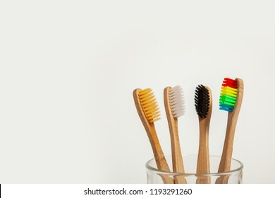 Set of toothbrushes in glass on gray background. Concept toothbrush selection, bamboo eco-friendly. Concept of sexual minorities and LGBT community