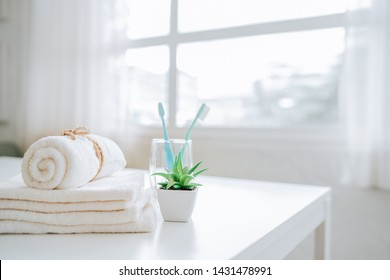 Set with toothbrushes and white towels on table