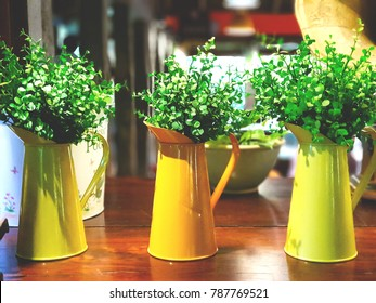 Set of topiary trees in the yellow pots on wooden table, selective focus. Interior design with natural concept