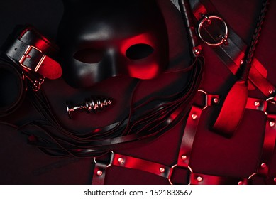 set of toys for BDSM sex. Leather Flogger, handcuffs, belt, choker, mask and metal anal plug