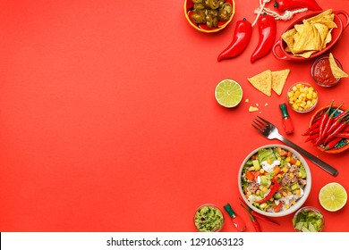 Set of traditional mexican dishes - burrito bowl, nachos, guacamole and salsa dressing, chili peppers, chopped jalapeño and lime on red background. Overhead view, flat lay, copy space