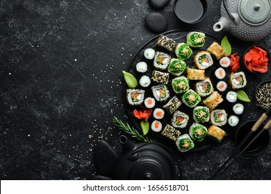 Set of traditional sushi on a black plate. Sushi and rolls on a dark background.