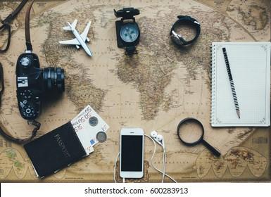 Set for travel are passport, money, camera, notebook, smartphone, clock, binoculars, airplane and vintage map.