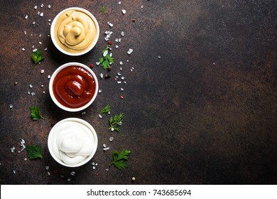 Set of tree classic sauce - ketchup, mayonnaise and mustard on dark rusty stone or metal background. Top view with copy space.