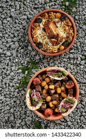 Set of Two Asian Dishes with Lyavangi and Jiz-biz in Natural Ceramic Bowls on Rustic Background Top View. Roasted Quail with Rice and Grilled Liver, Heart and Lungs with Potatoes on Gravel Texture