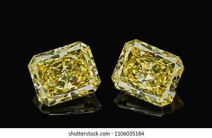 Set of two luxury yellow transparent sparkling gemstones emerald cut shape diamonds isolated on black background.