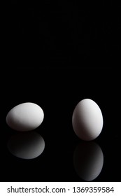 A set of two white eggs on a vertical mirror black background with reflections of the pair.  One standing on end with the other laying on its side with copy space.