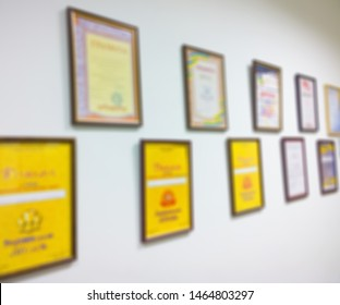 A set of unrecognizable various certificates, patents, diplomas and awards in wooden frames on the wall of the office. Abstract blurry background image for business. - Shutterstock ID 1464803297