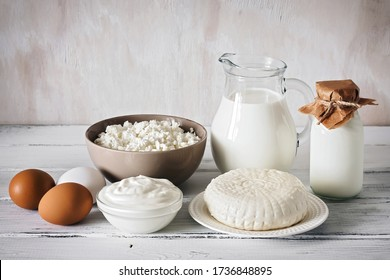 Set a variety of dairy products on a white wooden rustic table, side view. Milk, cottage cheese, cheese, sour cream, yogurt, eggs