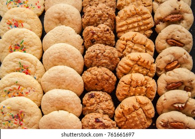 Set of various american style cookies on a black stone background. Shortbread with confetti, snickerdoodle, peanut butter, oatmeal and pecan cookies.