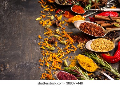 Set of various aromatic colorful spices in old vintage spoons and herbs on a dark wooden background. Ingredients for cooking. Top view