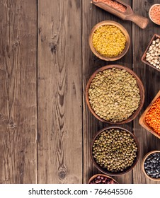 Set of various beans and colorful lentils in bowls and box on wooden background, top view with copy space.