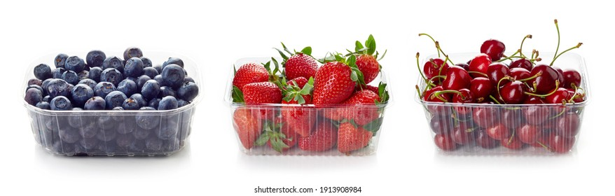 Set of various berries - blueberry, cherry and strawberry in plastic transparent container box, isolated on white background