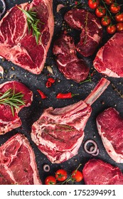 Set of various classic, alternative raw meat, veal beef steaks - chateau mignon, t-bone, tomahawk, striploin, tenderloin, new york steak. Flat lay top view on gray stone cutting table