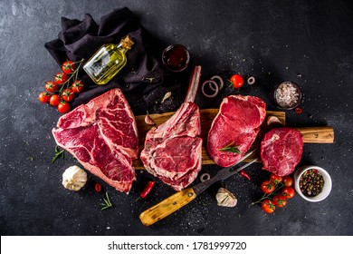 Set of various classic, alternative raw meat, veal beef steaks - chateau mignon, t-bone, tomahawk, striploin, tenderloin, new york steak. Flat lay top view on black stone cutting table