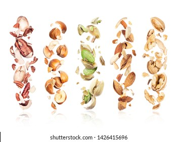 Set of various crushed nuts in the air on a white background