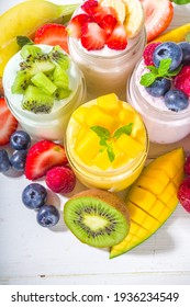 Set of various fruit and berry sweet yogurts in glass jars. Variety healthy Breakfast yoghurt with blueberry, strawberry, mango, kiwi, raspberry, with fresh fruits and berries, white wooden background