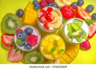 Set of various fruit and berry yogurts in glass jars. Variety healthy Breakfast yoghurt with blueberry, strawberry, mango, kiwi, raspberry, trendy bright yellow background with hard light dark shadows