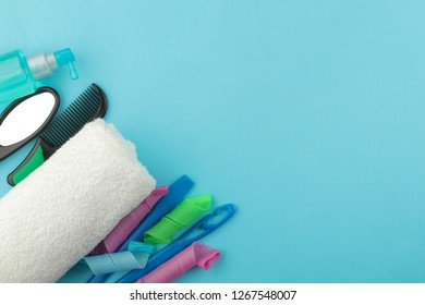 A set of various hair combs and mirror and hair cosmetic on a white towel on a bright blue background. view from above. with space for text