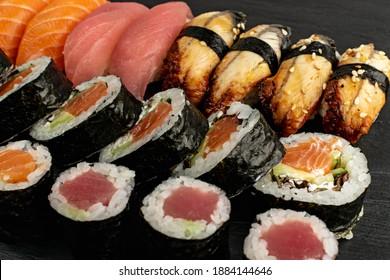 Set of Various Japanese Sushi Food on Dark Sate Plate Closeup. Nigiri and Nori Maki Sushi Rolls with Raw Salmon, Maguro Tuna, Unagi Eel, Avocado, Cucumber, Green Salad and Philadelphia Cheese
