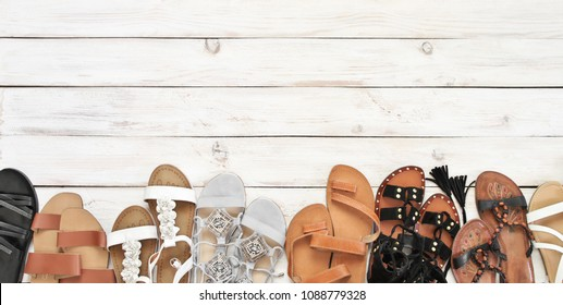 Set of various leather sandals on white wooden floor. Casual summer footwear, top view point.